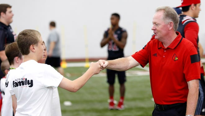 Louisville's coach Bobby Petrino fist bumps Tanis Wilkes from Lawrenceburg. Kids from Kosair Children's Hospital hung out and ran drills with the U of L football team Saturday morning. Wilkes, a member of Brave Hearts, had two open heart surgeries before he was one. July 18, 2015
