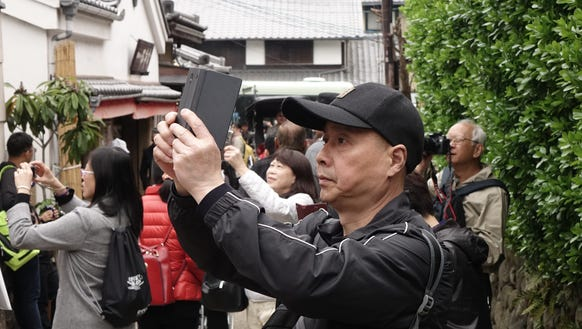 Tourists snapping away on smartphones near Kyoto, Japan.