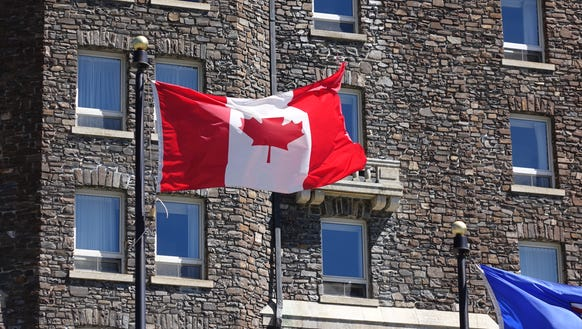The Canadian flag waves in front of the Fairmont hotel