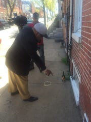 On Wednesday, Wilmington City Councilman Michael A. Brown points to a casing at the fatal shooting scene.