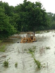 This equipment sits on what used to be a ridge off Louisiana Highway 1 near Natchitoches. Like the rest of owner Glyn Davis' pastureland, it's been claimed by the flooded Red River.