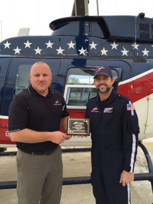 Program Director Justin Dearing, left, presents Flight Paramedic Jason Bourg with the Region 4 Paramedic of the Year award.