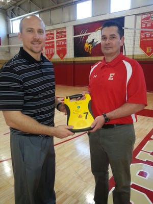 Edison High School health and physical education instructor Mark Blevins and Edison High School certified athletics trainer Tim Root hold the AED on the same court where they saved the life of a Colonia High School basketball player on Tuesday night.