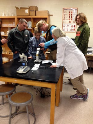 Karla Bouck shows her zoology students and Josh Baker's veterinary science students how to determine viability of bull semen samples in a science lab at Mountain Home High School Career Academies.
