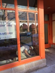 Keith Schemenauer of Thorson Paint helps ready 305 Third Street for Kidz Corner, a shop that focuses on children's used clothing.
