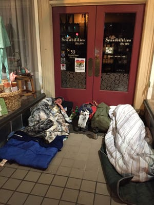 A photo showing people camping outside downtown businesses.