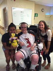Genevieve Vereb (left) and Ivy West (right) pose with Sam Woodard after they delivered flowers to him on Saturday at the Titusville Nursing Home.