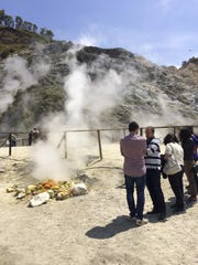 Visitors look at steaming fumaroles at the Solfatara crater bed, in the Phlegraean Fields near Naples, Italy. The fields comprise a sprawling constellation of ancient volcanic centers.