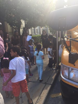 Parents and children gather around a school bus at Cross Hill Academy in Yonkers to practice bus safety.