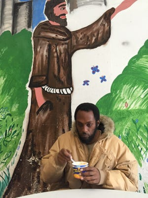Stephon Wolde-Tinsaye eats macaroni and cheese with hot sauce at Saint Joseph's House of Hospitality on South Avenue in Rochester.