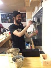 Stephen Kocher of Pennsauken pours a beer behind the bar at Eclipse Brewing in Merchantville.