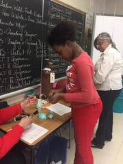 Sixth-grader Jahzara Jones of Southbridge learns the mechanics of hot air balloons with an egg carton, a helium balloon and weights.