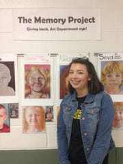 Seneca High School art major Jennifer Mackey with the portrait she and other classamtes drew of orphans in war-torn eatern Ukraine.Teh art will be sent to the chilrend by the charitable Memory Project. Her artwork is at the top left center