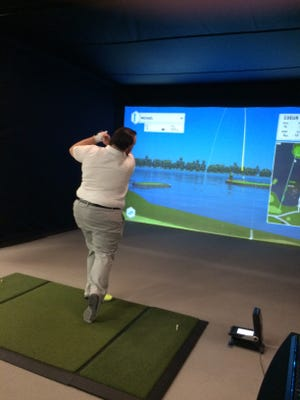 Caleb Enerson checks out his ball flight during a practice session this winter with the help of the Foresight Sports golf simulator installed in close proximity to the indoor practice range at SentryWorld.