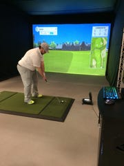 Caleb Enerson works on his golf game during a winter afternoon with the help of the Foresight Sports golf simulator installed in close proximity to the indoor practice range at SentryWorld.