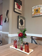 Personal touches such as fresh flowers, vintage-style artwork, and hand-carved salt and pepper mills (made by a local artist) add to the charm of The Farmhouse in Cherry Hill. Red accents brighten up the earthy tones of the restaurant.