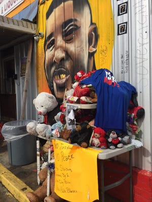 Trinkets and sign cover a memorial outside the Triple S Food Mart where Alton Sterling was shot and killed last year.