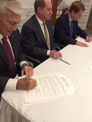 Health care executives sign an agreement to merge home health services. From left: John Lloyd, co-CEO of Hackensack Meridian Health; Kevin Slavin, CEO of St. Joseph's Healthcare System; and Robert Garrett, co-CEO of Hackensack Meridian Health.