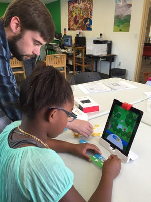 Muncie Public Library Digital Mentor Stuart Cotton helps a young customer with a Digital Climber activity at Connection Corner in this photo from 2017.