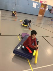 "Students in Stangel Elementary School physical education teacher Jamie Ullman's class participate in the ""Shipwrecked"" activity, which teaches teamwork and cooperation."
