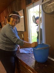 Wolcott Keeper's House volunteers  Lynn Madden and Cara Yeager tackle the window cleaning from both sides.