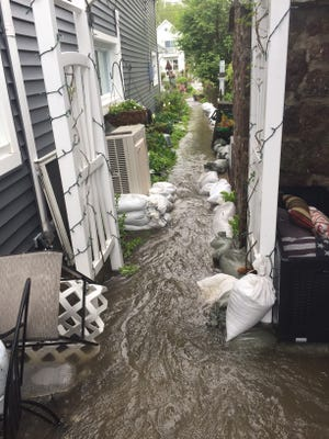 Water coming in through a front door and rushing alongside the house and onto the street at an Edgemere Drive house on May 24, 2017.