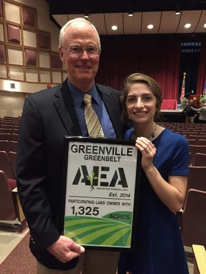 Larry Bentle, left, of the Greenville Land Stewardship Committee, presents Hannah Goulet with a copy of her artwork and a $500 check for her design of the logo for the Greenville AEA.