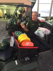 Lt. Frank Forte of the Escambia County Sheriff's Office hands out giveaway items such as Frisbees and sunglasses to his deputies at a 5 a.m. meeting before the beach air show on July 7.