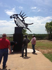 City of Wichita Falls parks and recreation crew members and director Tery Points, left, installed a sculpture of a fishing fish this fall at Lake Wichita. It was donated by the Robert Seabury family.