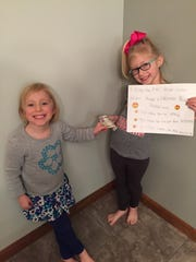 Claire Ambrose, right, collects $5 from her sister