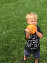 Lachlan Sabo, 2, tries flinging a pumpkin. His mom, Erin Sabo, is helping to create the Highland Fall Festival.