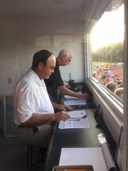 WMRN radio sportscaster Jeff Ruth with color analyst John Kuzio, near, get ready to call Ruth's 500th high school football game at Pleasant last year. Ruth will continue to call area high school football and basketball games on the radio.