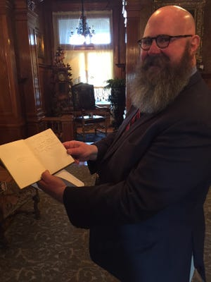 Pabst Mansion Executive Director John Eastberg shows one of around two dozen old books belonging to members of the Pabst family that were donated Thursday. The books were found at the former Renaissance Book Shop, which was recently demolished.