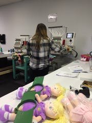 A seamstress personalizes dolls at Dibsies Personalization