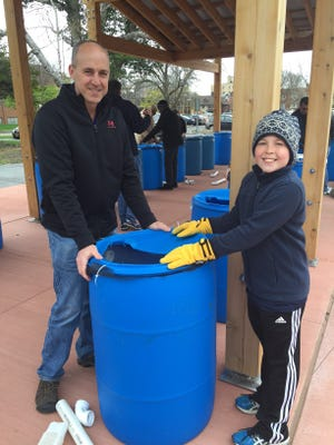 Participants put the lid on their barrel at the D and C Earth Day Rain Barrel Workshop