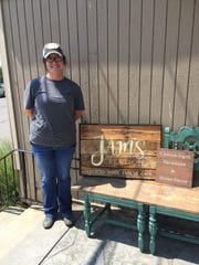 Owner Jami Fadley stands by her store sign and restored
