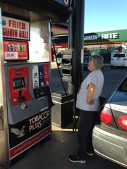 Theresa Nugent of Lena fills her car with $1.99 gas Monday. Gas prices have not been as low since 2009.