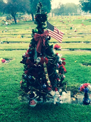 A Christmas tree was placed at this grave marker in California.
