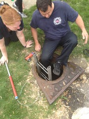 An Indianapolis firefighter is shown preparing to enter a storm drain in an effort to find a lost puppy on the afternoon of May 20, 2014, on Indianapolis' Eastside. The puppy was eventually rescued and returned to its owners.