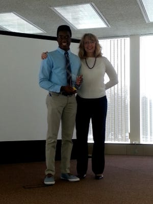 Win Adissem, a Harding High School senior, was recognized as the Student Volunteer of the Year by United Way of Marion County during Wednesday's luncheon. Presenting the award is United Way Executive Director Pam Stone.