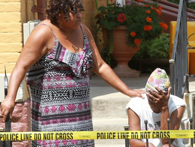 A woman is comforted at the scene of  a shooting in the 300 block of E. 13 th Street, Covington.