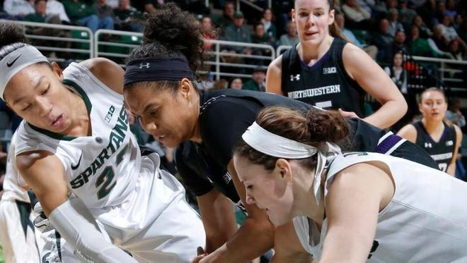 Michigan State's Aerial Powers, left, Northwestern's Nia Coffey, center, and Michigan State's Tori Jankoska battle for the ball Sunday, , in East Lansing. Michigan State won 74-51.