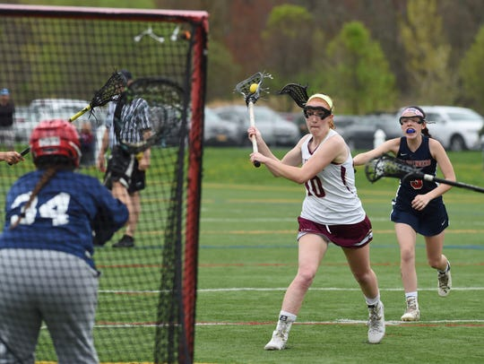 Arlington's Abby Carlin, center, goes for a shot during