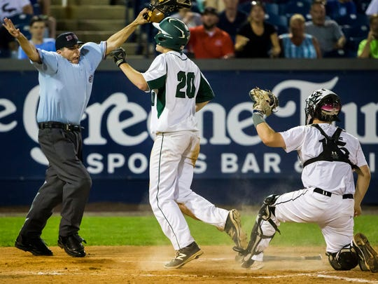 Home plate umpire Greg Huff shows the safe sign after St. Mark's  Christopher Ludman (No. 20) slid in safely under the tag of Caravel's Colin Adams in the bottom of the sixth inning of the DIAA Baseball State Championship game at Frawley Stadium in Wilmington on Tuesday evening. Ludman's run turned out to be the winner for St. Mark's as they defeated Caravel 5-4.