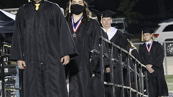 The Denison High School class of 2020 lines up during graduation ceremonies. Officials with DISD and SISD plan to move forward with traditional ceremonies.