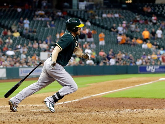 Oakland Athletics' Brandon Moss watches his RBI-single drop to score Jed Lowrie during the ninth inning of a baseball game against the Houston Astros Tuesday, July 29, 2014, in Houston. (AP Photo/David J. Phillip)