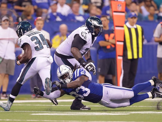 Indianapolis Colts outside linebacker Erik Walden (93) dives for the feet of Philadelphia Eagles running back Kenjon Barner (34) as he runs out of the backfield during the first half of an NFL football game Saturday, Aug. 27, 2015, at Lucas Oil Stadium.