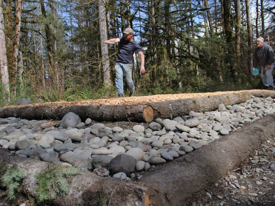 Ira Burgess throws off the renovated tee box on hole No. 2 at the refurbished disc golf course at Camp Taloali in Stayton.
