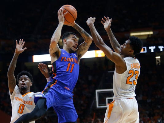 Florida guard Chris Chiozza (11) is defended by Tennessee guards Jordan Bone (0) and Jordan Bowden (23) during the second half of an NCAA college basketball game Wednesday, Feb. 21, 2018, in Knoxville, Tenn. (AP Photo/Crystal LoGiudice)