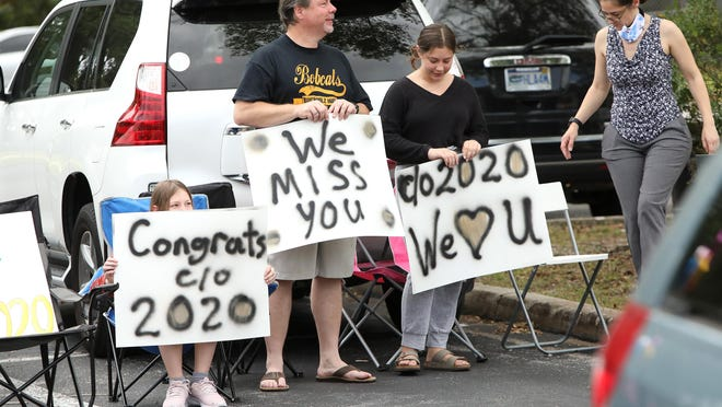 Teachers and staff cheer for the Buchholz High School senior class of 2020 during a drive-thru celebration in the school parking lot on May 16. Other schools in the area are doing similar recognitions within social distance guidelines due to the coronavirus pandemic as administrators weigh options for ceremonies.